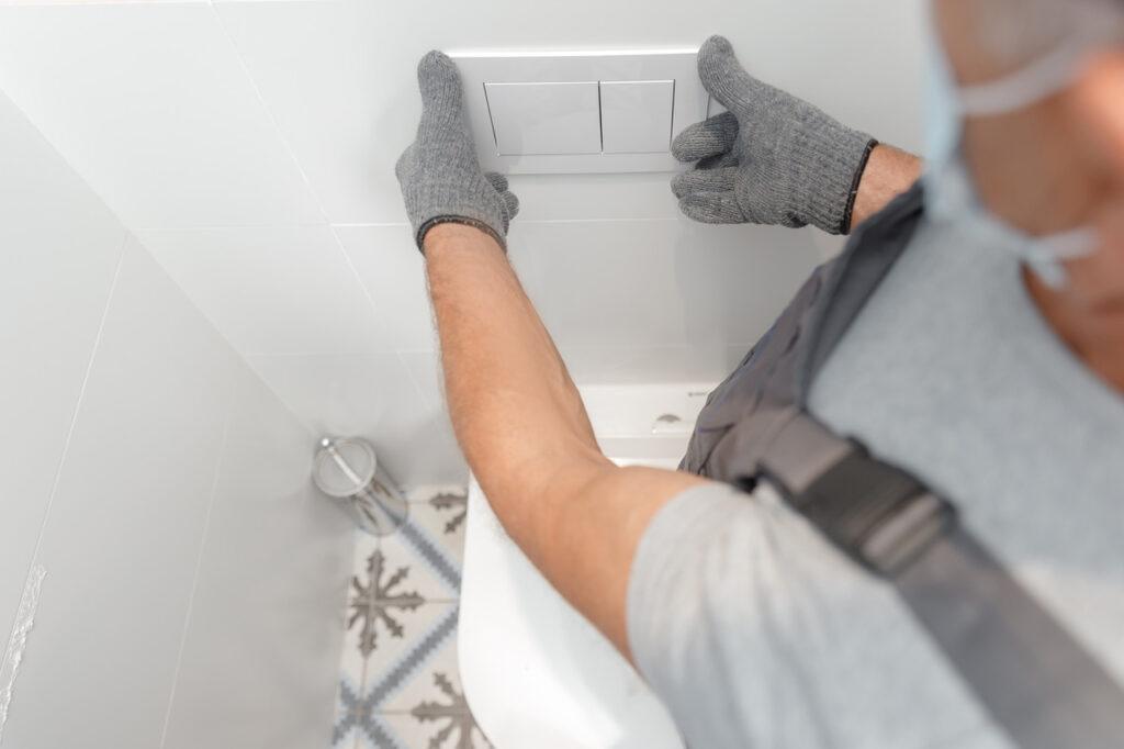 Plumber in medical mask installing toilet bowl in restroom, work in bathroom.