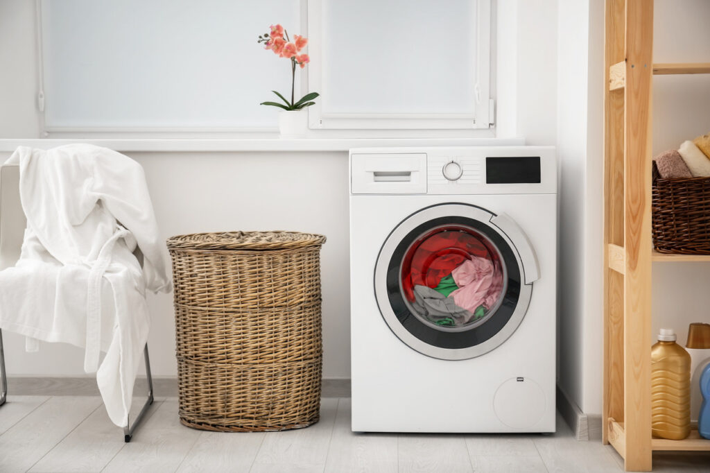 Laundry in washing machine and basket indoors